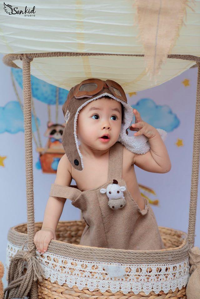 Hình ảnh bé trai tinh nghịch trong buổi chụp hình thôi nôi với trang phục đơn giản