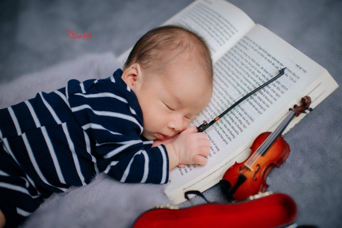 Ảnh bé dễ thương trong tư thế cầm sách đọc